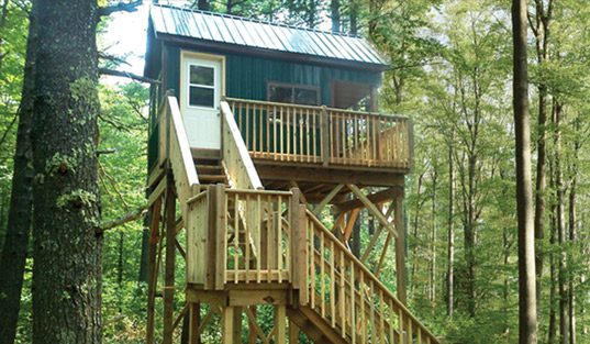 small-cabin-with-sleeping-loft-and-deer-blind-windows-tucked-in-forest