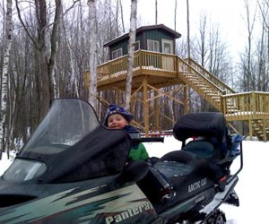 boy-sitting-on-snowmobile-in-front-of-cabin