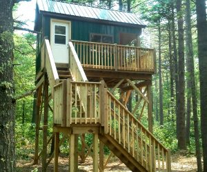 green-metal-cabin-with-porch-staircase-nestled-in-trees