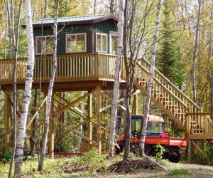 utv-parked-under-staircase-of-cabin-in-woods